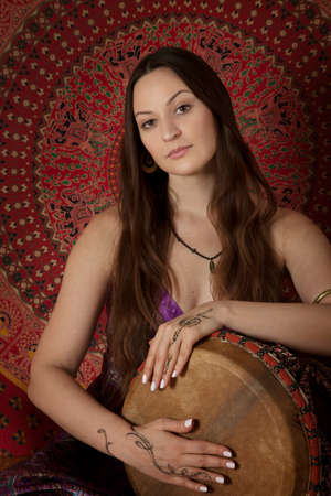 young adult woman: Young adult woman playing drum during meditation session