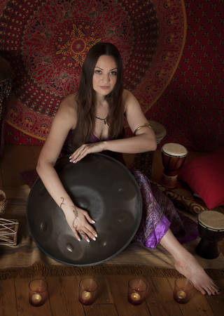 melodic: Female artist performing indoors playing hand pan