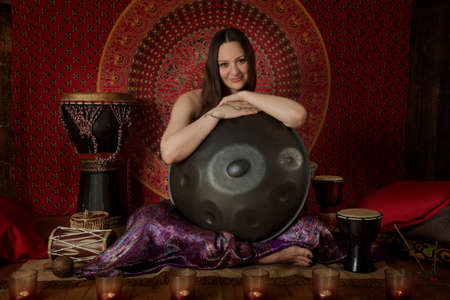 melodic: Attractive Caucasian woman with hand pan indoors