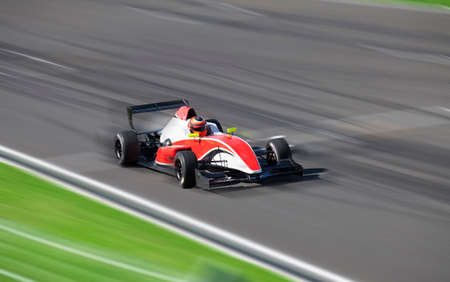 one: Bolide Formula 2.0 driving at high speed with motion blur in circuit