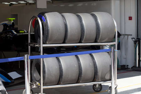 utilized: Wheels   are standing in row in the rack next to the garage Stock Photo
