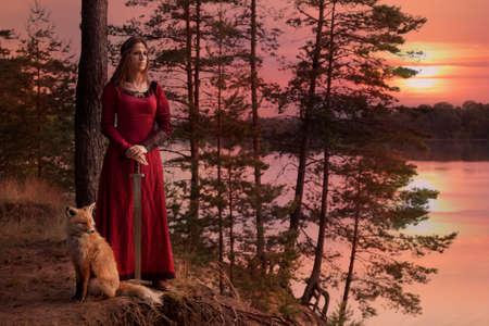 夕日に対してフォックスと、川のそばに立っている剣で中世の服の若い女性