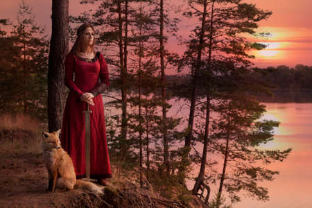A young woman in medieval clothes with a sword stands beside the river, with a Fox against the setting sun
