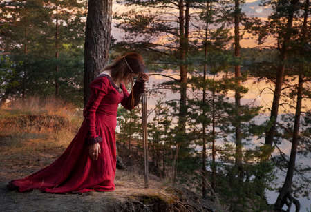 A young woman in medieval clothes with a sword praying outdoors Фото со стока