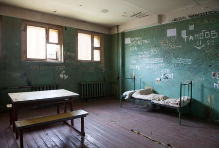 penitentiary: Dark prison cell with dirty walls and metal bad at abandoned Penitentiary Stock Photo