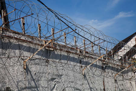 prison system: Old abandoned prison white wall with metal barbed fence in blue sky background