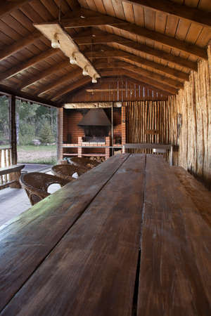 indoor inside: Covered veranda of a country house with long wooden table Stock Photo