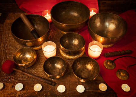Studio shot of Tibetan singing bowls with burning candles Imagens