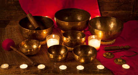 tibetan singing bowl: Set of Tibetan singing bowls and bells with burning candles on a red background
