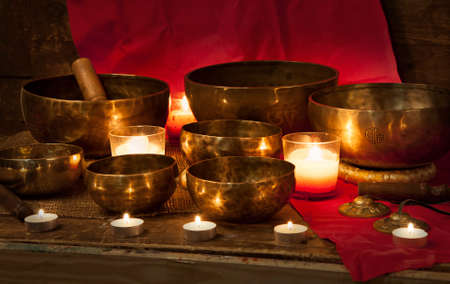 Tibetan singing bowls with burning candles on a red background Stock fotó