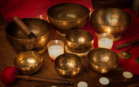 チベットの歌ボウル、赤の背景に非常に熱い蝋燭と鐘