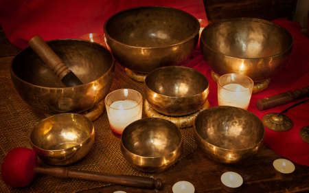 Tibetan singing bowls and bells with burning candles on a red background