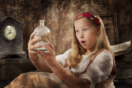 timepiece: Portrait of a beautiful young girl expresses wonder holding the magic potion in her hands dressed as Alice in Wonderland indoor