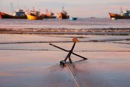 steadfast: An anchor on the beach with soft wave and fishing boats on a background