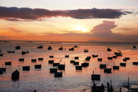 ne: Dark silhouettes of Vietnamese round fishing boat-baskets in the setting sun. Mui Ne, Vietnam  Stock Photo