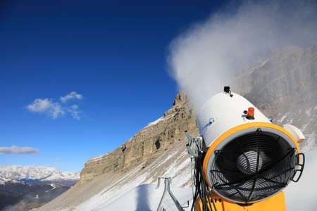 pressurized: Snow cannon against the blue sky. Snow-making is the production of snow by forcing water and pressurized air through a snow gun or snow cannon, on ski slopes