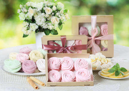 Multicolored homemade zephyr or marshmallows in the box on a white table with a bouquet of flowers