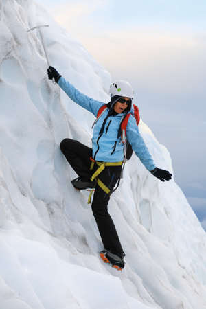 cold: Girl dressed in a blue jacket and helmet on her head using ice axe climbs on Falljokull Glacier (Falling Glacier) in Iceland