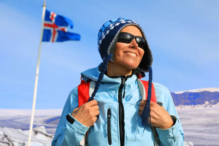Portrait of a young female tourist with backpack on the background of waving Icelandic flag and glaciers, Iceland
