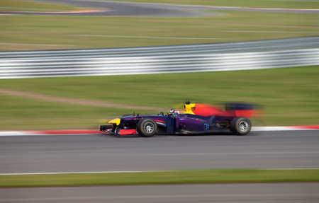 Formula 1.0 race car racing at high speed with motion blur on a racing track
