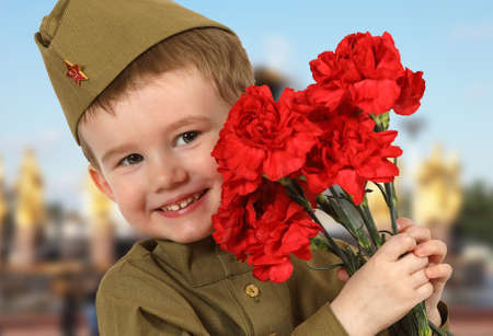 Portrait of little boy in Soviet military uniform with a bouquet of red carnations on the background of blue sky Stock Photo