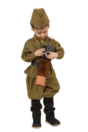 The little boy dressed in the old-fashioned Soviet military uniform with retro photo camera isolated on white background