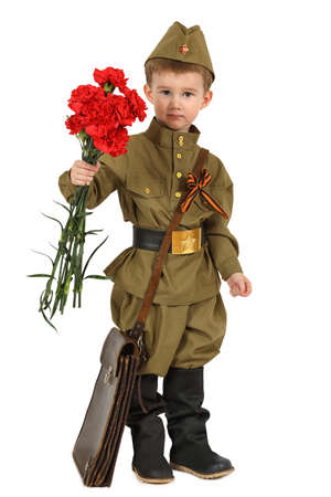 The little boy in the old-fashioned Soviet military uniform with a bouquet of red carnations isolated on white background