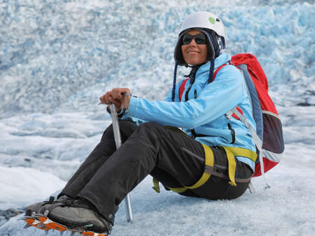 Young woman climber sitting with an ice pick in her hand on a Falljokull Glacier (Falling Glacier) in Iceland