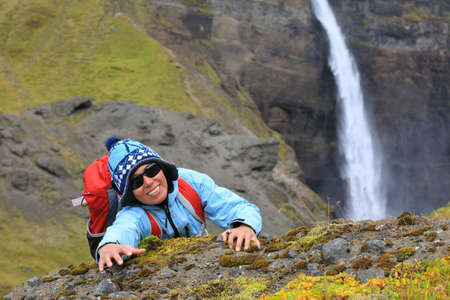 Young tourist woman with backpack climbing to the top of the rock on the background of amazing scenery with waterfall, Iceland
