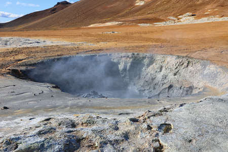 Volcanic boiling mud pots surrounded by sulfur hot springs in Hverir Namafjall geothermal place in Iceland Stock Photo