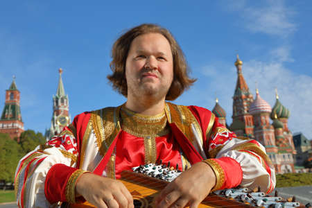 Songster in traditional Russian clothes plays an old Russian musical instrument gusli on the background of the Kremlin and St. Basil's Cathedral on red Square. Moscow, Russia Stok Fotoğraf