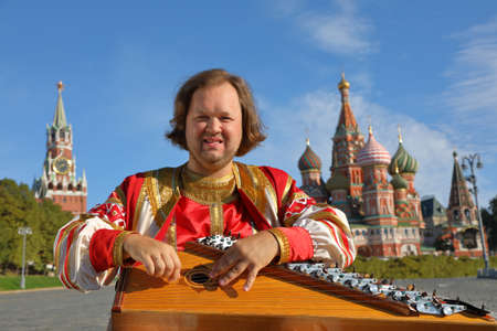 The minstrel in traditional Russian clothes plays an old Russian musical instrument gusli on the background of the Kremlin and St. Basil's Cathedral on red Square. Moscow, Russia Stok Fotoğraf