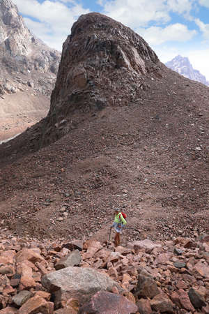Young woman hiker stands at the foot of Bear mountain in Tian Shan mountains. Kazakhstan, Almaty region Stock Photo