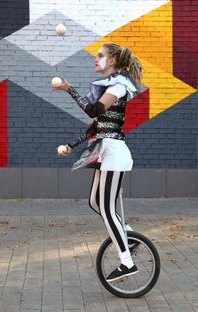 Girl clown rides a unicycle and juggles balls  in front of colorful wall outdoors Stock Photo