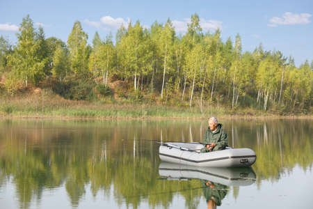 An elderly fisherman concentrates on catching the crucian from his boat. Banco de Imagens - 112265353
