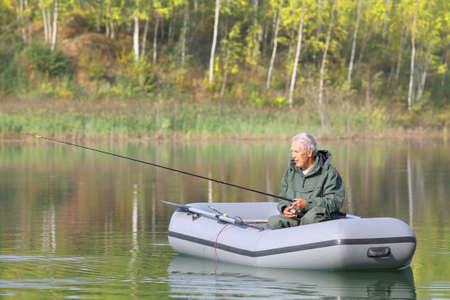 An elderly fisherman concentrates on catching the fish from his boat on a sunny autumn day
