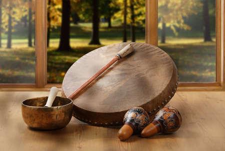 Una natura morta del tamburo sciamanico, delle campane tibetane e delle maracas sullo sfondo della foresta