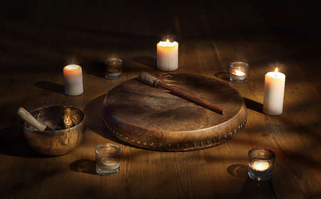 Shaman tambourine and Tibetan bowl surrounded by candles in a dark room