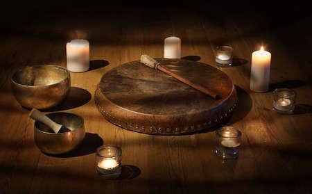 Pandereta chamán y cuenco tibetano con velas en una habitación oscura