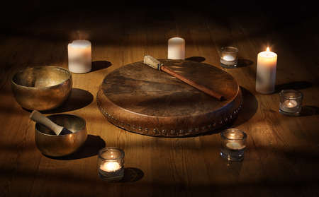 Shaman tambourine and Tibetan bowl with candles in a dark room Stockfoto