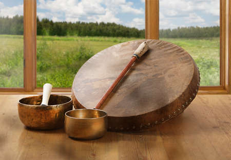 A still life of the shamanic drum and Tibetan singing bowls on a background of green fields and forests