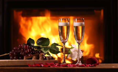 Two glasses of sparkling wine and a fruit plate, chocolate and rose on the background of a burning fireplace