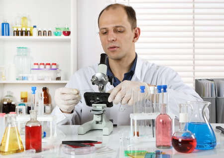 Young scientist working in the laboratory, he adjusts the microscope to conduct experiments