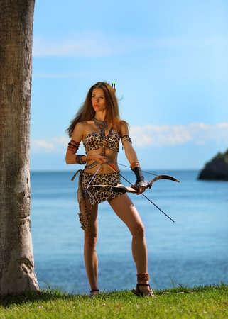 Ein junges schönes Amazonenmädchen mit Bogen bereit auf einem Hintergrund des Meeres und des blauen Himmels