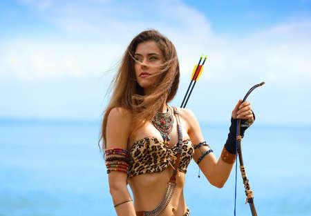 Porträt eines jungen schönen Mädchens in einem Amazonas-Kostüm mit Pfeil und Bogen auf dem Hintergrund des Meeres und des blauen Himmels