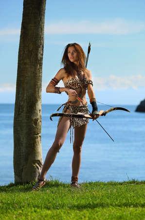 Una joven hermosa en un traje de Amazon con un arco y flechas sobre un fondo de cielo azul y mar Foto de archivo