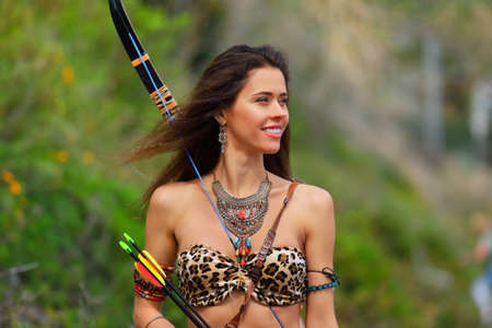 Portrait of a young woman in an Amazon costume with a bow and arrows on a background of green vegetation