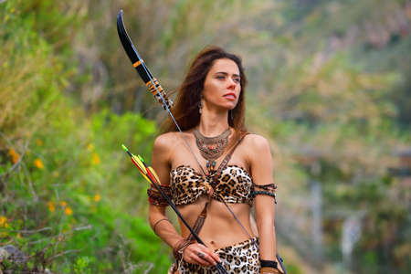 Portrait of a young beautiful girl in an Amazon costume with a bow and arrows on a background of green vegetation