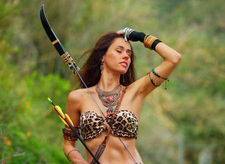 Retrato de una hermosa joven amazona con un arco y flechas sobre un fondo de vegetación verde