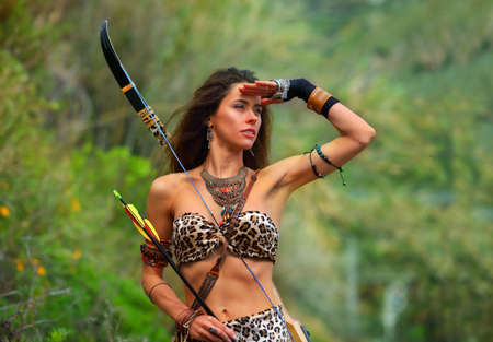 Portrait of a young attractive girl in an Amazon costume with a bow and arrows on a background of green vegetation